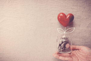 Charitable donations change jar with a heart on top
