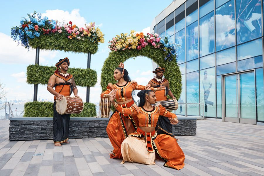 Performers pose in front of Empire Outlets logo