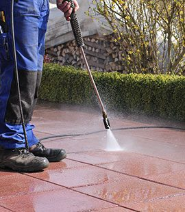 A worker performs power washing services.