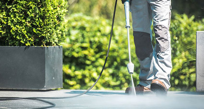 A workers completes a power washing services job.